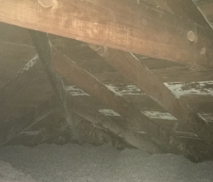 wood planks in an attic with grey and white discoloration