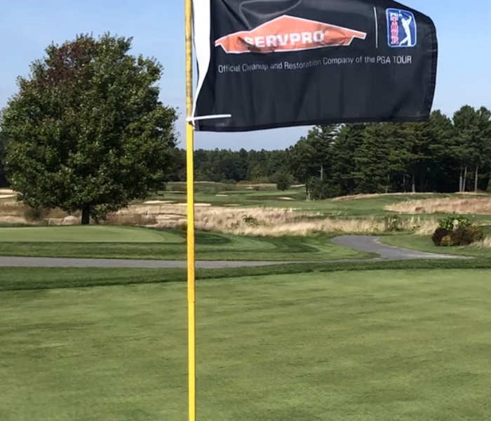 a golf course with a SERVPRO flag coming out of the hole