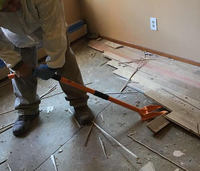 a man removing wood flooring