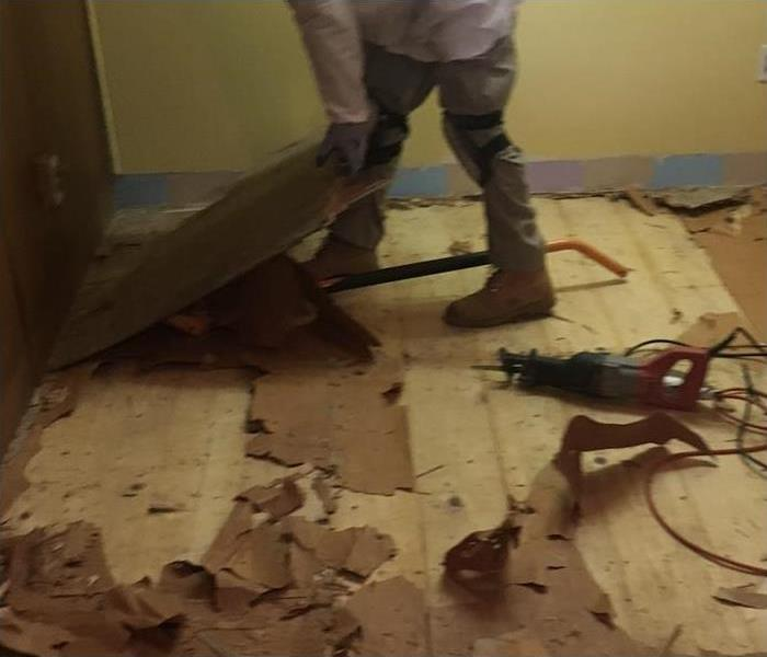 A man replacing the flooring of a home. Floor damaged by water