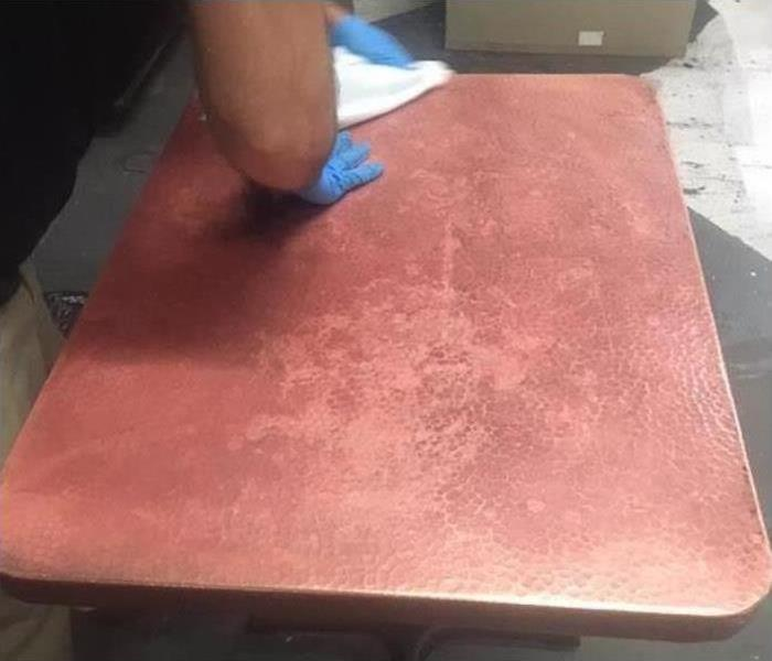 Professional cleaning a table after fire damage